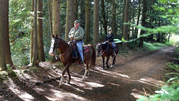 Gold Creek Trail horseback riders Case Zegstroo (left) and Kim Boag ride through the forest to a beaver pond clearing. LARRY STEAGALL / KITSAP SUN