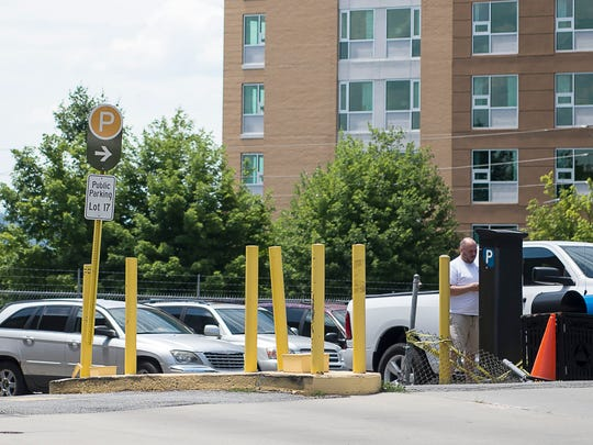 A visitor pays for parking at the public lot on O Henry Avenue Friday July 1, 2016.