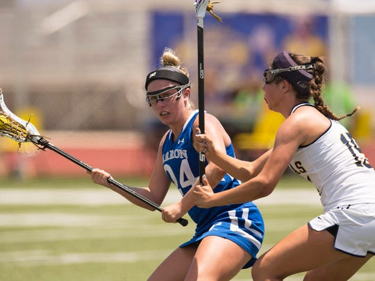 Barron Collier's Jo Imbriani (left) drives the ball upfield as St. Thomas Aquinas' Caroline Stefans applies defensive pressure in the first half of their semifinal game during the FHSAA Lacrosse State Championships at Jupiter High School Friday, April 28, 2017. Barron Collier lost 9-12.