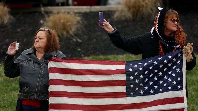 People hold the American Flag and pay respects during the funeral procession for firefighter Patrick Wolterman.