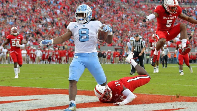 RALEIGH, NC - NOVEMBER 25:  Michael Carter #8 of the North Carolina Tar Heels beats Dexter Wright #14 of the North Carolina State Wolfpack for a touchdown during their game at Carter Finley Stadium on November 25, 2017 in Raleigh, North Carolina.  (Photo by Grant Halverson/Getty Images)