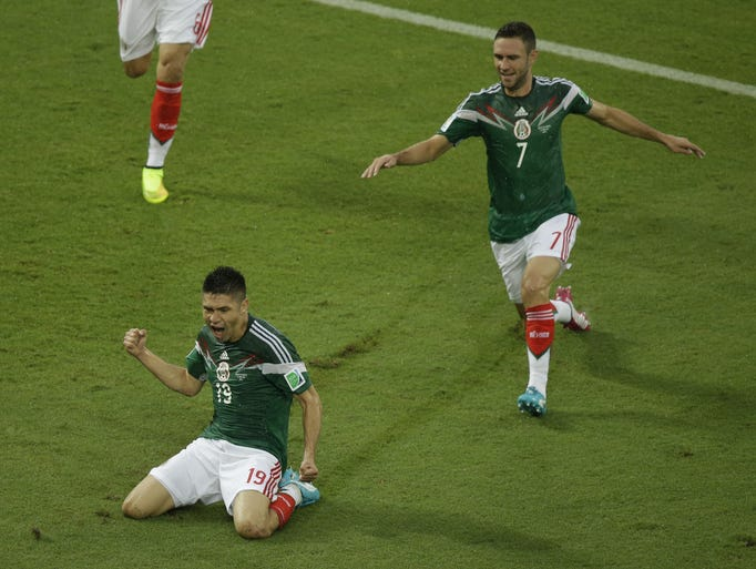 Mexico's Oribe Peralta celebrates after scoring during the group A World Cup soccer match between Mexico and Cameroon in the Arena das Dunas in Natal, Brazil, Friday, June 13, 2014.