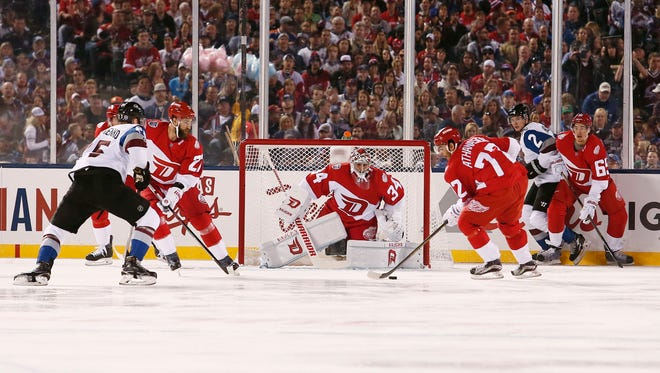 Red Wings center Andreas Athanasiou (72) controls the puck as goalie Petr Mrazek (34) looks on in the first period of the Stadium Series hockey game against the Colorado Avalanche at Coors Field on Saturday.