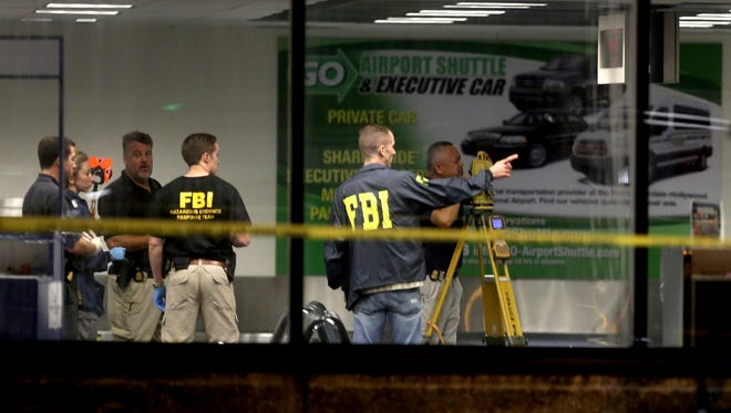 Investigators work in Terminal 2 at Fort Lauderdale-Hollywood International Airport on Jan. 7, 2017, the day after a shooting in the baggage area.