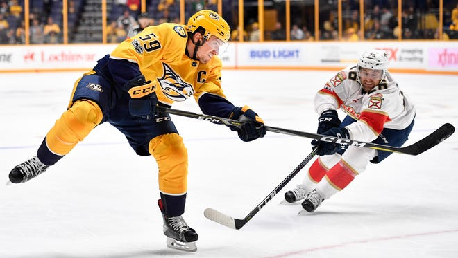 Predators defenseman Roman Josi (59) shoots past Florida Panthers forward Harry Zolnierczyk (26) during the first period in the second game of a preseason doubleheader Tuesday, Sept. 19, 2017, at Bridgestone Arena.