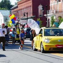 Dolores Higareda behind the wheel of her yellow Volkswagen Beetle leads the way for the Ulysses Philomathic Library's fancifully-decorated bookmobile in the Trumansburg Fireman's Parade on Saturday. Approximately 400 books were given away to area children.