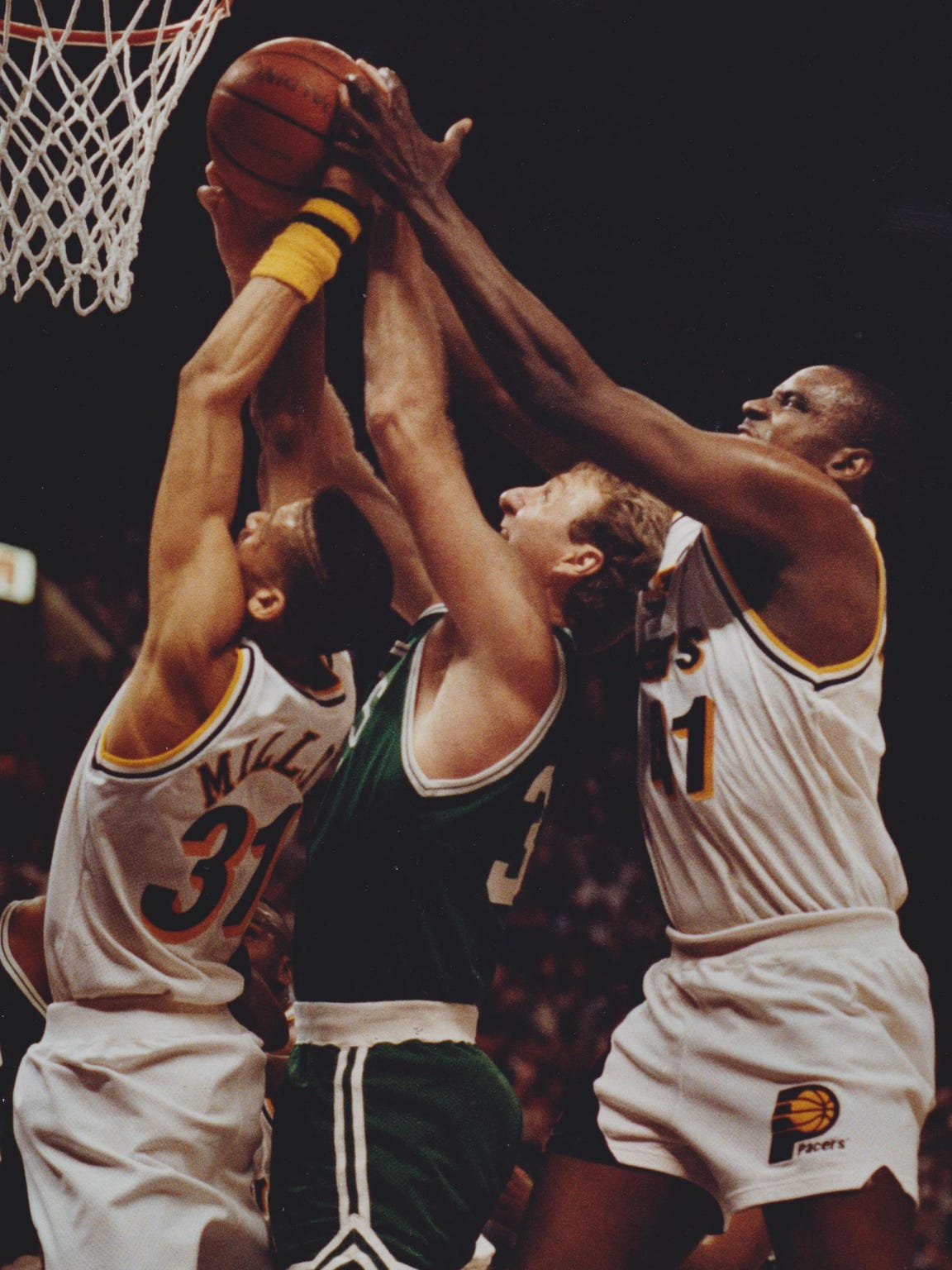 Larry Bird, middle, battles Reggie Miller, left, and