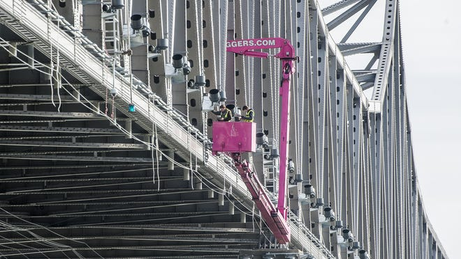 A crew works suspended above the Illinois River on Wednesday, October 21, 2020, among the multitude of lights attached to the Murray Baker Bridge in Peoria as part of the months-long upgrade of the bridge.