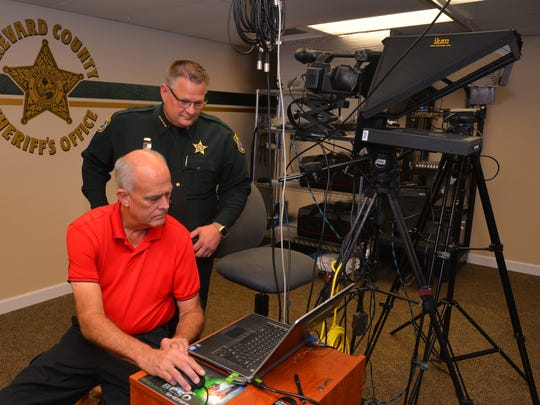 Sheriff Ivey stands in the media production center in Titusville talking with Ray Dils, the media production engineer. The sheriff has stepped up the sheriffs office visibility on social media including the popular and successful Wheel of Fugitives. Sheriff Wayne Ivey standing in the production Center.