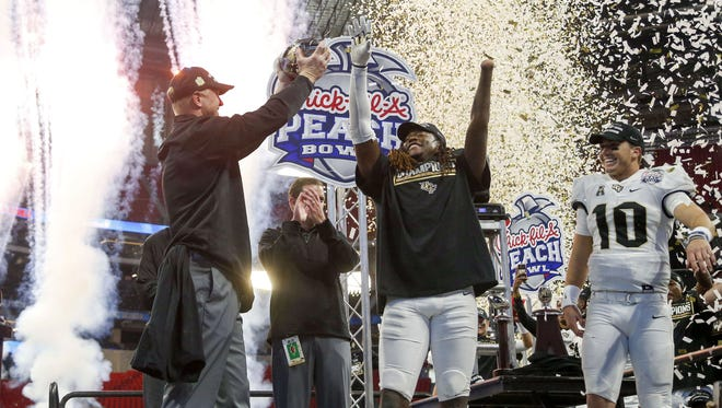 Central Florida Knights head coach Scott Frost, linebacker Shaquem Griffin and quarterback McKenzie Milton celebrate their Peach Bowl victory against Auburn.
