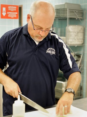 Jeff Hebl works in the kitchen creating a meal for the New Holstein Football team Thursday September 4, 2014 at the school. Hebl, a police officer by day job and a cooking competitor created a meal for the hungry Huskies.