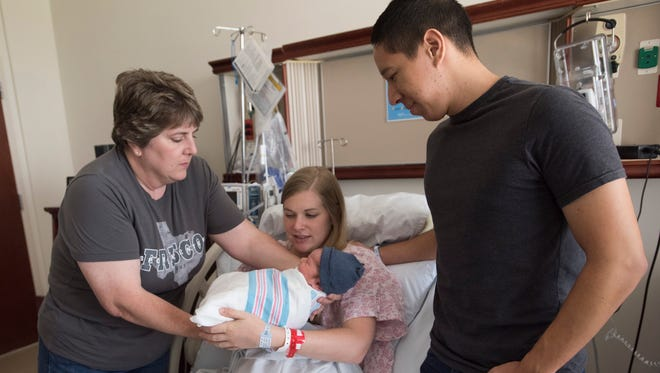 New grandmother, Chris Moen, left, hands over new grandson, James, to his parents, Michaela and Jacob Bishop after caring for the newborn at the Pensacola Naval Hospital on June 29, 2018. James, who was born on the 28th of June will be the last scheduled child to be delivered at the hospital.