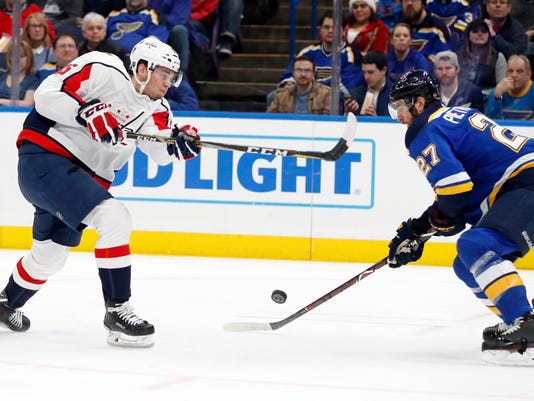 Washington Capitals' Andre Burakovsky, left, mishandles the puck while taking a shot as St. Louis Blues' Alex Pietrangelo defends during the first period of an NHL hockey game Monday, April 2, 2018, in St. Louis. (AP Photo/Jeff Roberson)