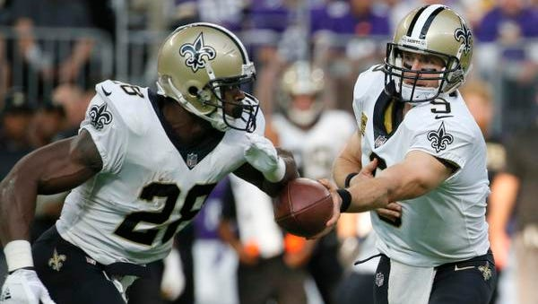 New Orleans Saints quarterback Drew Brees (9) hands the ball off to running back Adrian Peterson during the first half of an NFL football game against the Minnesota Vikings, Monday, Sept. 11, 2017, in Minneapolis.