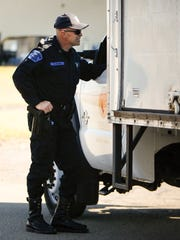 Michigan State Police motor carrier Sgt. Brett Black talks to a trucker during a stop on Nov. 4, 2015 near Jackson. The driver had rolled through a stop sign at an I-94 off-ramp.   Black gave the driver a warning after his driving record checked out in Black's in-car computer.
