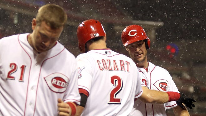 The Reds' Todd Frazier, left, heads to the dugout after scoring on a home run by Ryan Ludwick, right, as Zack Cozart congratulates Ludwick in the fourth inning at Great American Ball Park.