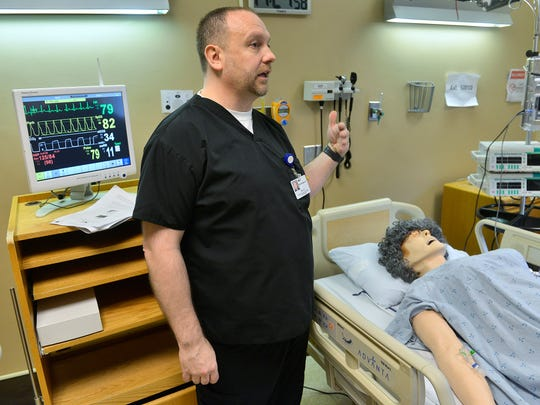 CentraCare Health Media/Simulation Specialist Jim Kiess explains Dec. 17 that another of the mannequins, Pat, can be made to simulate either sex, breathe, sweat, cry tears, have lifesigns, measure administered medicines, and other functions. There are four separate mockup rooms in St. Cloud Hospital that comprise the simulation lab, used to practice for situations and patient care.
