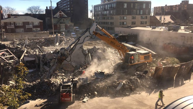 Crews clear the scene in the 1800 block of N. Farwell Ave. in MIlwaukee on Monday after debris from a demolition filled the street.
