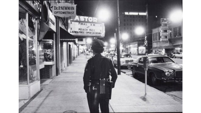 Akron Police Officer Rosalyn Bowens walks the night beat in 1978 near the Astor Theater on South Main Street.