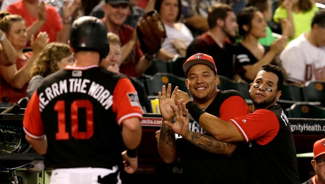 Arizona Diamondbacks pitcher Taijuan Walker (99) and David Peralta (6) celebrate after Chris Herrmann (10) scores a run on a past ball in the third inning against the San Francisco Giants at Chase Field.
