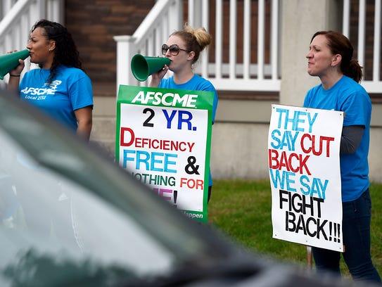 Ashlynn Rufe, Elizabeth Harnish and Eva McBride participate in the strike against Cedar Haven Nursing Home Monday, Oct. 23, 2017.