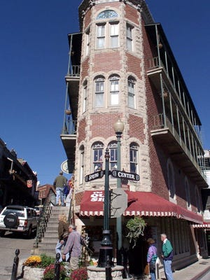 Tourists walk past the Flatiron Building in downtown Eureka Springs, Ark.