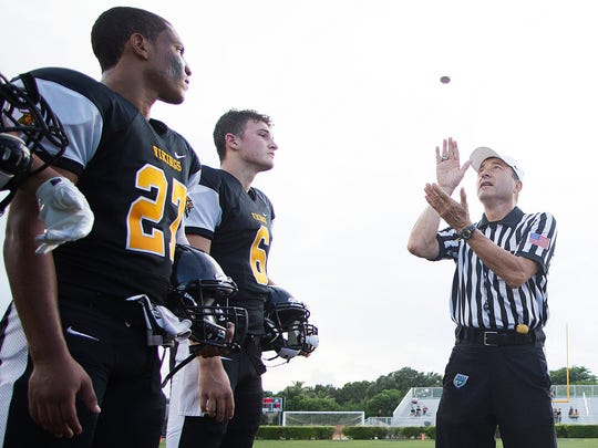 John Mantica of the South Gulf Officials Association leads the coin toss between Bishop Verot High School and Estero before a game in south Fort Myers.