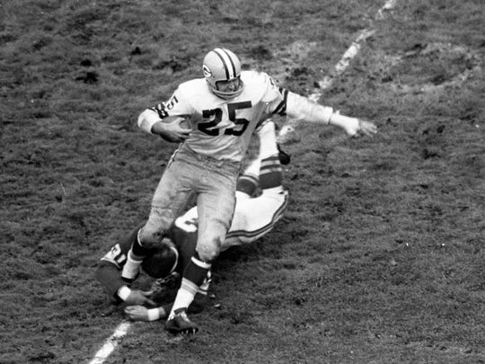 Green Bay Packers halfback Tom Moore (25) tries to elude Minnesota Vikings linebacker Clancy Osborne (31) after catching a short pass from Bart Starr at Metropolitan Stadium in Bloomington, Minn., on Oct. 22, 1961.