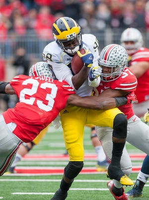 Michigan quarterback Devin Gardner is sandwiched by Ohio State safety Tyvis Powell, left, and linebacker Joshua Perry in the second quarter during their 2014 game in Columbus, Ohio.
