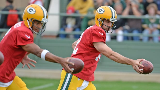 Quarterback Aaron Rodgers, right, and backup Brett Hundley run a drill during training camp practice.