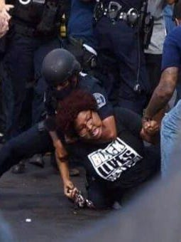 Information with this image from page 35 of a lawsuit, filed in U.S. District Court against Detroit police on Monday, claims an officer grabbed protestor Nakia-Renee Wallace from behind and slammed her to the ground, placing her in a chokehold.