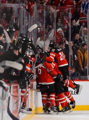 Team Canada players mob Max Domi after he scores against the USA.