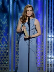 Amy Adams accepts the Golden Globe for best actress in a musical or comedy.