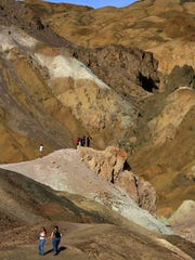 Hikers climb through the Artist's Palette in Death Valley National Park.