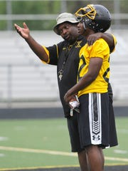 King's head coach Dale Harvel talks to one of the team members during Monday's practice. Photos of Martin Luther King High School's football team practicing at their Detroit school on Monday, Aug. 10, 2015.  (Elizabeth Conley/The Detroit News)