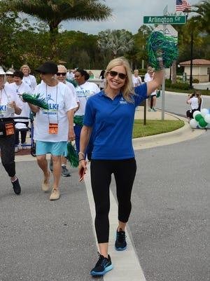 Fitness guru Chris Freytag leads residents of the Arlington retirement community on their walk.