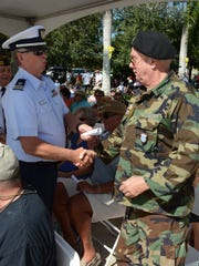 Coast Guard Auxiliary Commander Keith Wohtlman presents a proclamation to Vietnam vet Bill Filbin. Hundreds gathered at Veterans Community Park on Marco Island at 11 a.m. Friday to commemorate Veterans Day.
