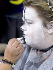 Michelle Kringel of West Bend applies cake makeup to daughter Alycia Kringel as one of the characters at The Haunt.