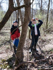 Mara Doles, left, and Grayson Withrow, right, find and take photos of a tree with paint on it to show how nature has been altered by humans at the Metahqua Nature Preserve