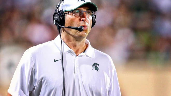 Aug 29, 2014; East Lansing, MI, USA; Michigan State Spartans defensive coordinator Mark Staten reacts to a play during the second half of a game at Spartan Stadium. MSU won 45-7. Mandatory Credit: Mike Carter-USA TODAY Sports