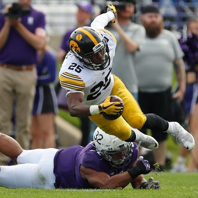 Iowa's Akrum Wadley (25) is tripped up by Northwestern's