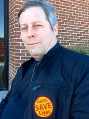 "Chris Hershberger wears a ""Guns Save Lives"" sticker"