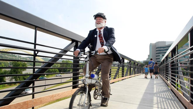 Frank Henson, president of bicycle advocacy group Queen City Bike, rides last summer across a bridge just east of the Purple People Bridge in Newport. It's the first leg of the Riverfront Commons project dedicated that day. A similar bridge will get built between the Taylor-Southgate Bridge and the Newport floodwall.