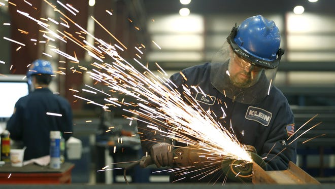 Saw operator Dave Young of Greece removes burrs at Klein Steel in Rochester.