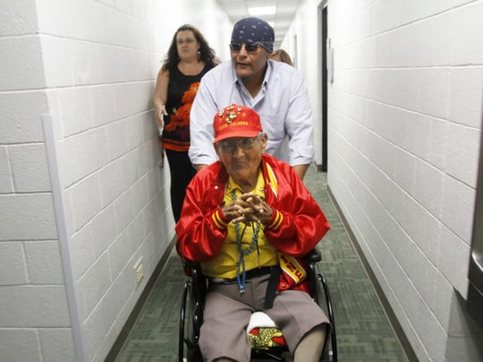 In a file photo from Thursday, Nov. 1, 2012 Navajo Code Talker Chester Nez is escorted in to the Henderson Fine Arts Center Performance Hall at San Juan College with his grandson Latham Nez, for a speaking engagement in Farmington, N.M.