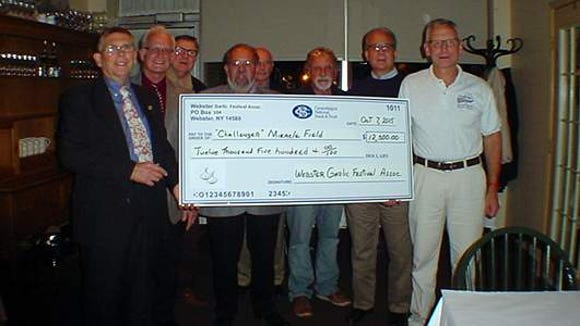 "(L-R) Webster Garlic Festival Association board members Rich Comins, Gary Lazzaro, Roger Awe, Bill Freeman, Harry Clauss, Whitey Proietti, Robert Anderson and Ron Kampff of ""Challenger"" Miracle Field"