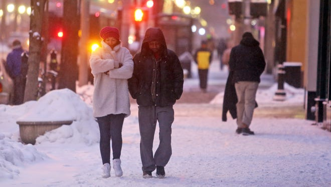 A couple brace themselves against the snow and wind as they walk on Mamaroneck Ave. in White Plains.