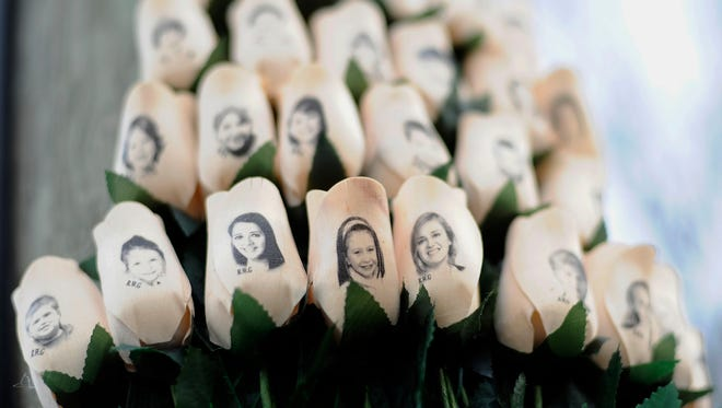 FILE - In this Jan. 14, 2013 file photo, white roses with the faces of victims of the Sandy Hook Elementary School shooting are attached to a telephone pole near the school on the one-month anniversary of the shooting that left 26 dead in Newtown, Conn.