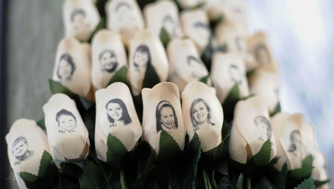n this Jan. 14, 2013 file photo, white roses with the faces of victims of the Sandy Hook Elementary School shooting are attached to a telephone pole near the school on the one-month anniversary of the shooting that left 26 dead in Newtown, Conn.