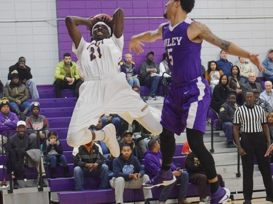 LSUA's Brandon Moss (21, left) is fouled by Wiley College's